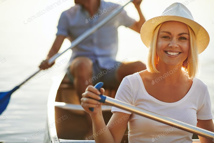 Smiling young woman canoeing with her boyfriend on a lake