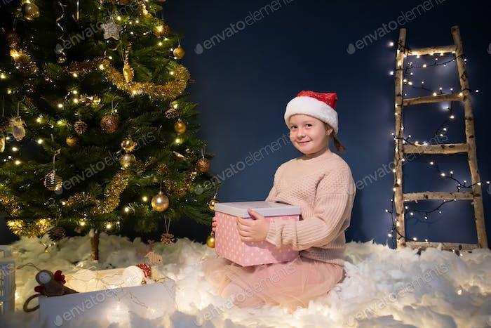 Weihnachten, Feiertage und Kindheitskonzept - cuti kleines Mädchen, das sich in der Nähe des Weihnachtsbaums amüsiert.