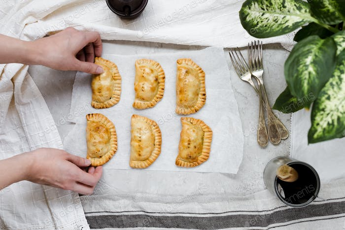 Woman Putting Homemade Empanadas on Grey Marble Table