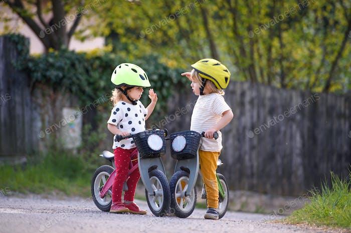 Kleine Kinder Jungen und Mädchen mit Helmen und Laufräder im Freien spielen