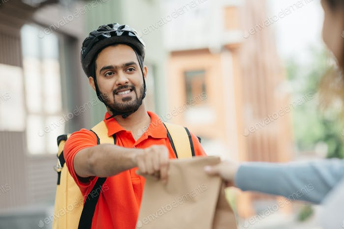 Takeaway restaurant food delivery. Portrait of young courier with beard in protective helmet and