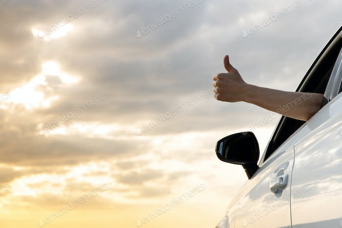 Man showing thumbs up/making Like / Ok sign with hand from car window