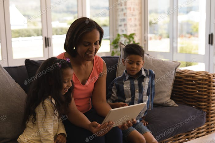 Multi-generation family using digital tablet while sitting on a wicker sofa in living room at home