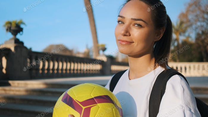 Beautiful sporty girl with backpack confidently looking in camera on the way to morning training