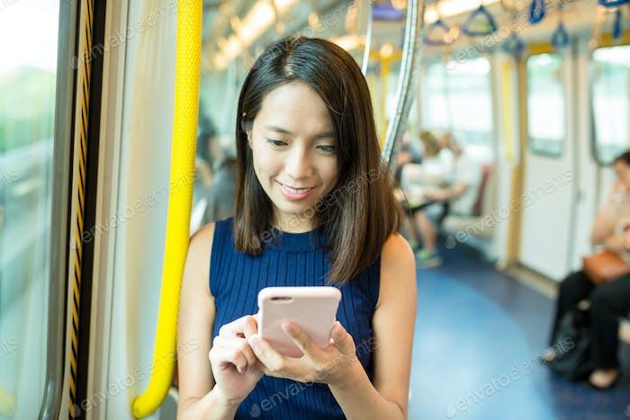 Woman using cellphone inside MTR in Hong Kong
