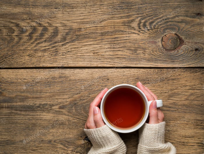 Female hands holding a mug of hot black tea. Cold winter