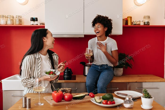 Positive girls sincerely laugh in kitchen. Curly girl drinks wine while her Asian friend eats veget