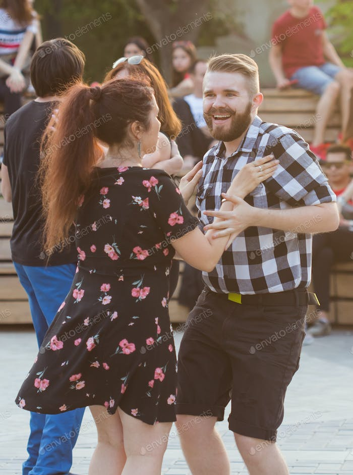Kizomba, bachata or salsa concept - beauty couple dancing social dance on open air party