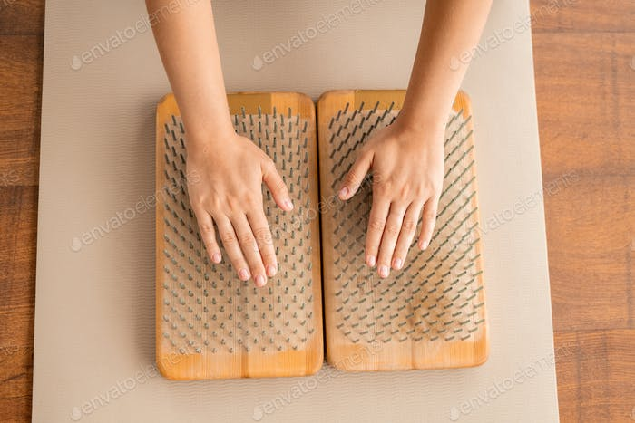 Hands of woman keeping her palms on metallic bristles of yoga massage pads