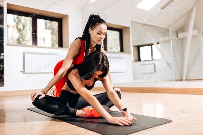 Slim girl dressed in black sports top and tights is doing stretching on the fitness mat with the