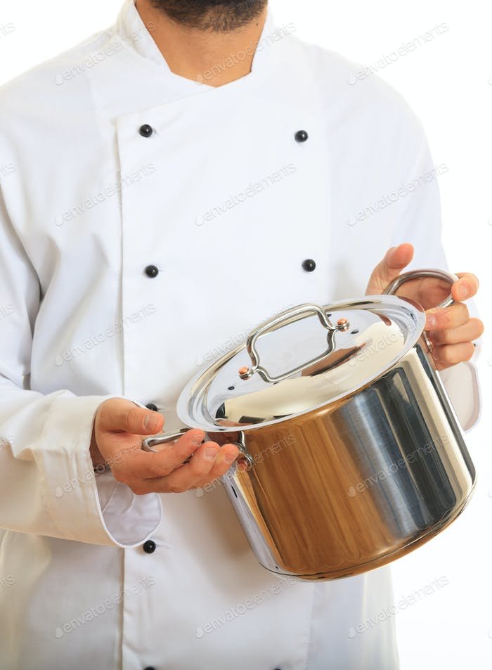 Chef with white uniform, holds a metal casserole, standing on white background.