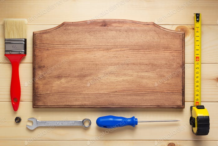tools at plank wooden board table background