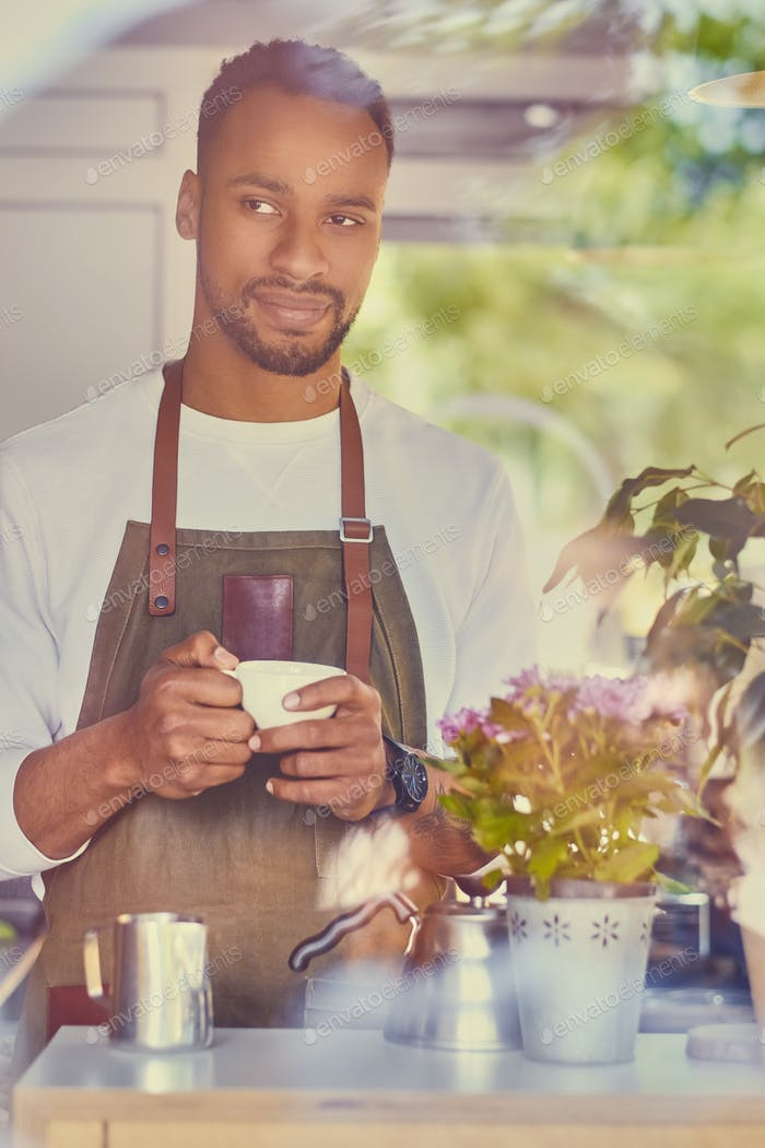 Schwarzer bärtiger Kaffee Verkäufer gießt Kaffee.