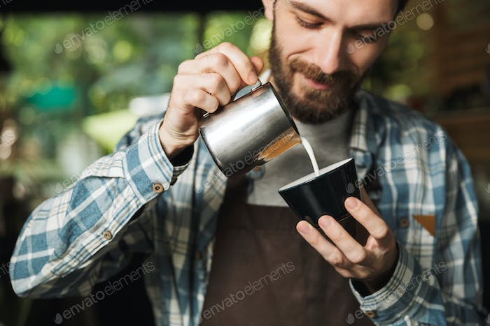 Image of joyous barista man making coffee while working in cafe