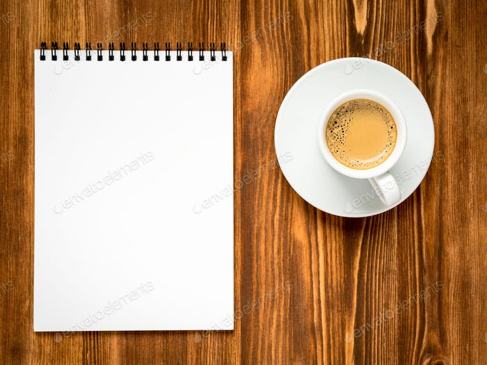 coffee in white cup and open notepad