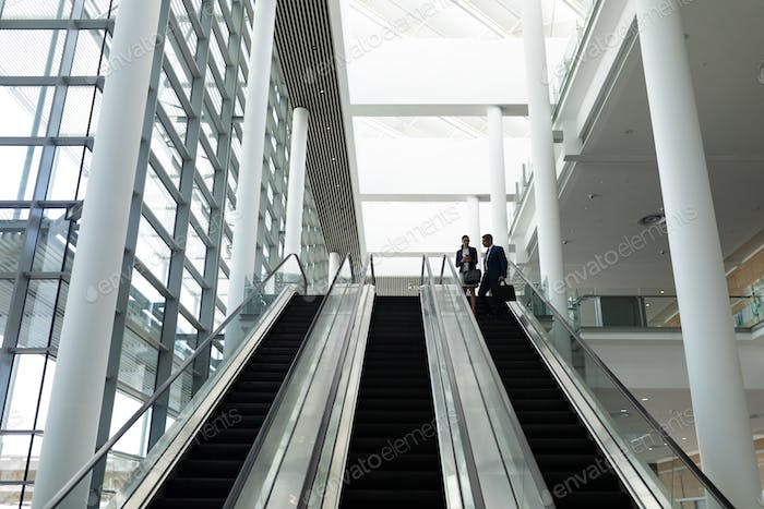 Businessman and businesswoman interacting with each other on escalator in office