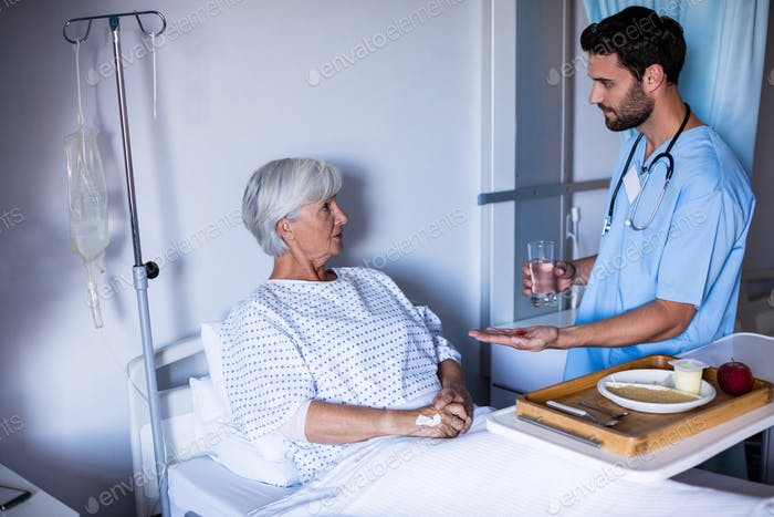 Doctor serving medicine to female senior patient on bed