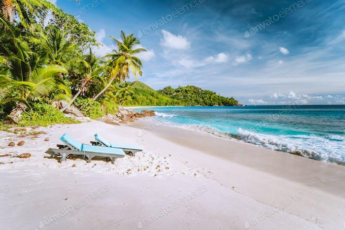 Mahe, Seychelles. Sun lounger at beautiful Anse intendance, tropical beach. Blue ocean waves, sandy