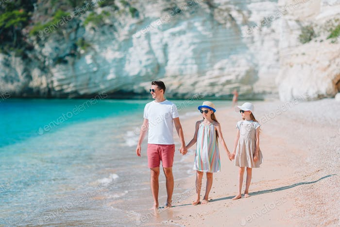 Отец и две дочери на пляже
