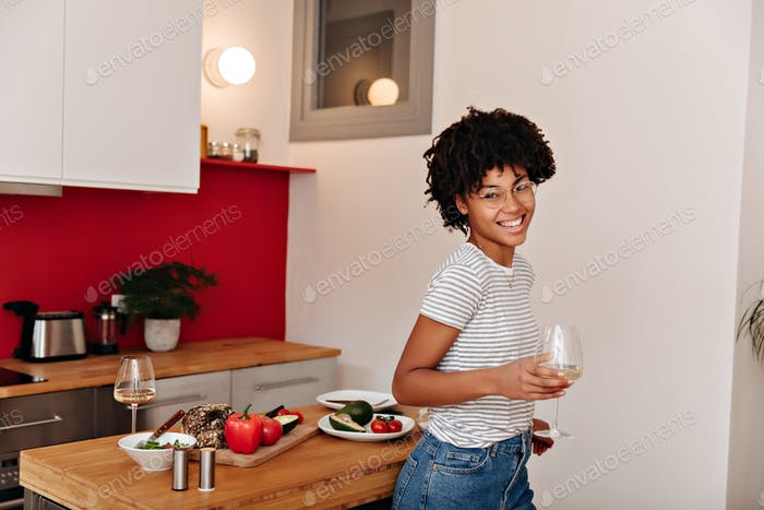 Charming girl in striped top laughs and holds glass of wine against background of kitchen with vege