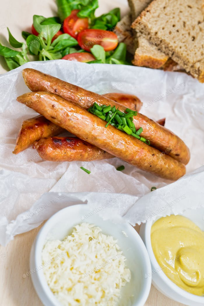 Fried sausage with mustard and horseradish, bread on wooden table
