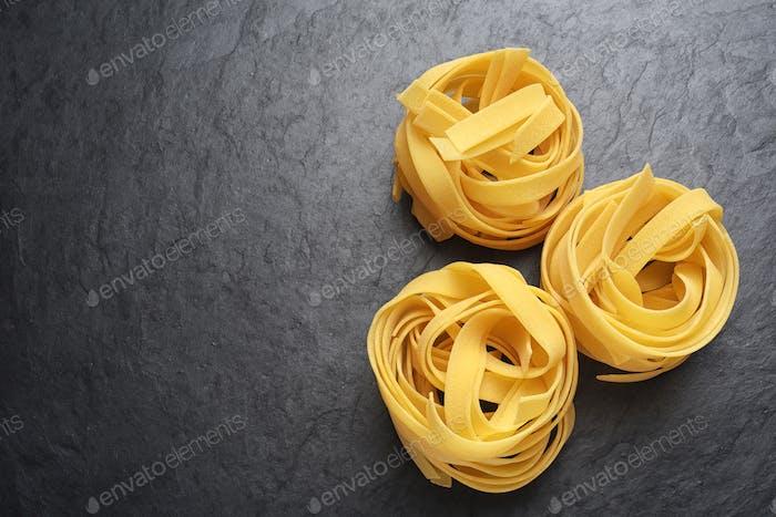 Fettuccine pasta on black background