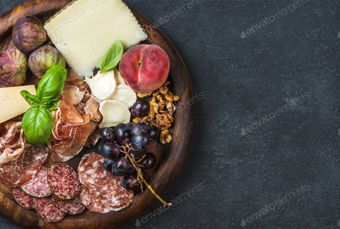 Italian wine snacks variety over dark plywood background, copy space