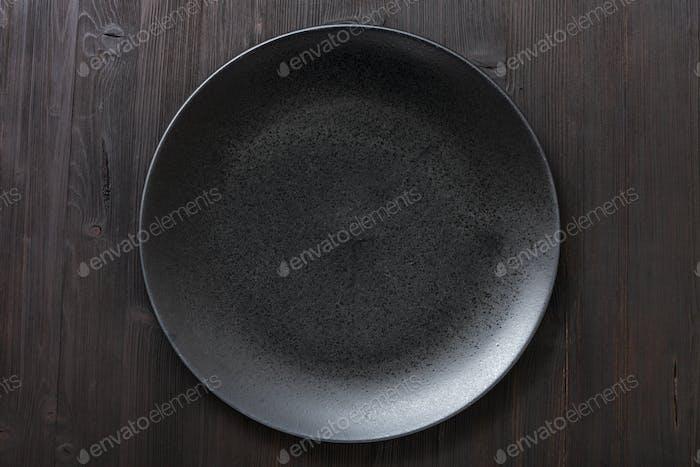 Draufsicht der schwarzen Platte auf dunkelbraunem Tisch