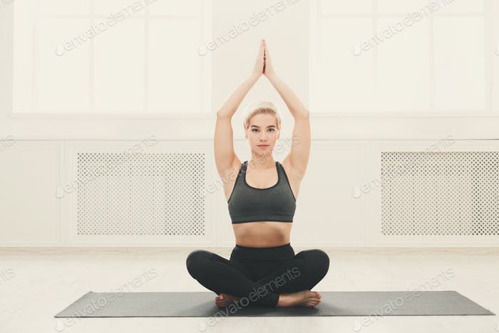 Young woman practicing yoga sitting in padmasana