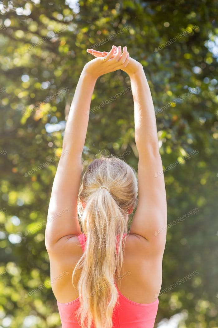 Active blonde stretching her arms in a park on a sunny day