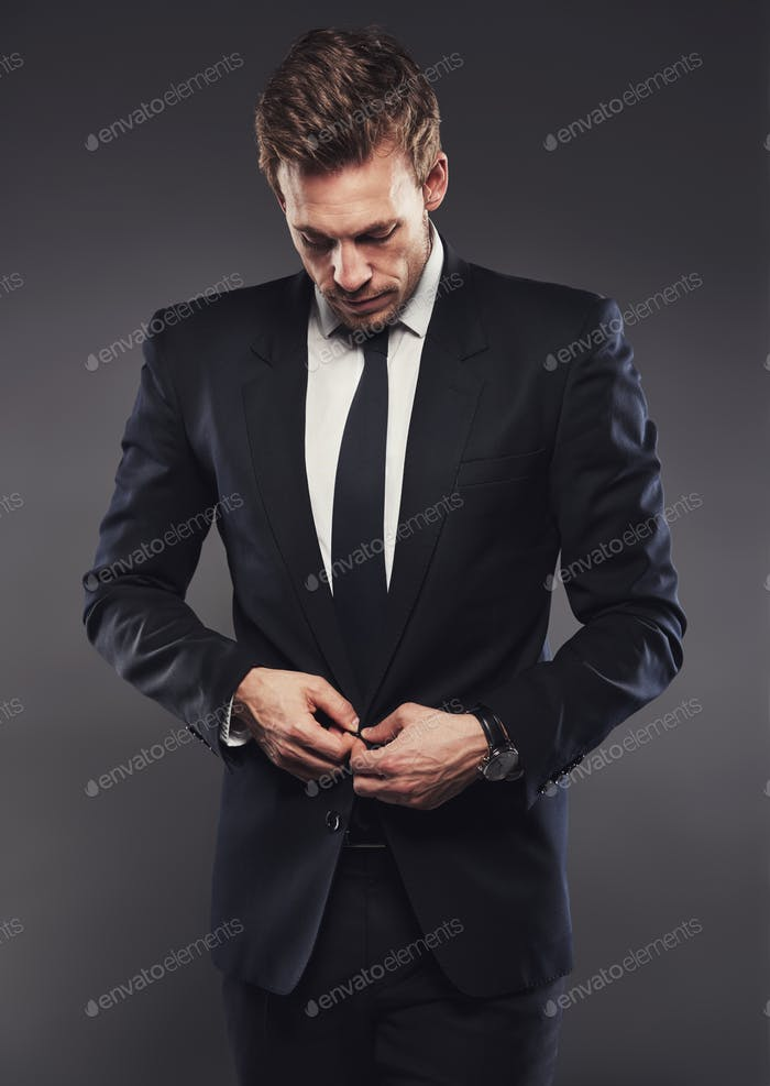 Stylish businessman in a suit standing aganst a grey background
