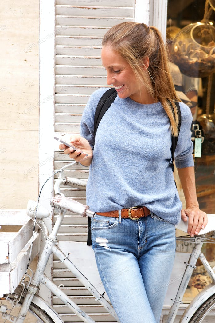happy woman standing with bicycle looking at mobile phone