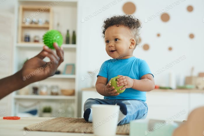 Laughing Baby Looking at Ball