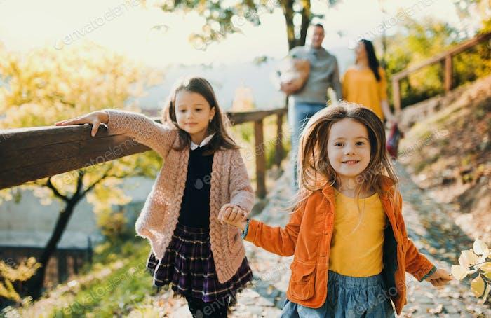 Dos niñas con padres irreconocibles en el Fondo caminando en el Parque en otoño.