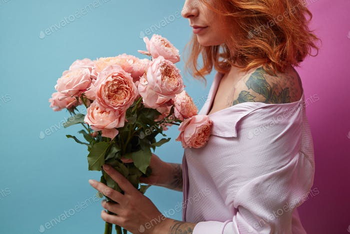 Gentle pink roses in the hands of a girl with a tattoo on a double pink blue background with copy