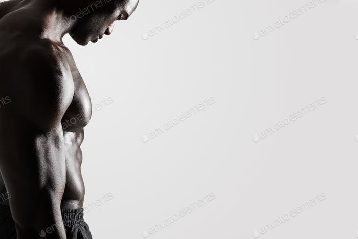 Young man with muscular body standing over grey background