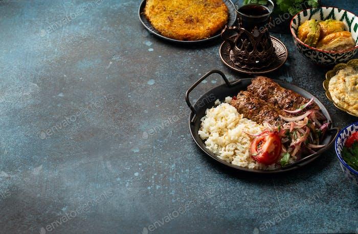Traditioneller türkischer Kebab mit Reis, Gemüse mit Vorspeisen und türkischem Tee