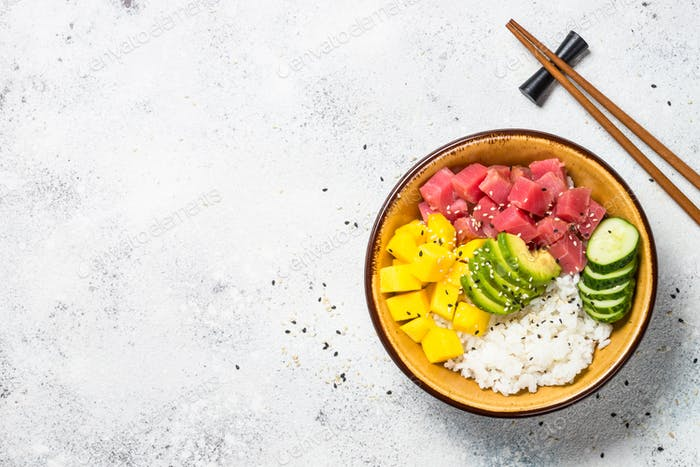Thunfischschüssel mit Reis, Avocado, Mango und Gurke auf weißem Tisch