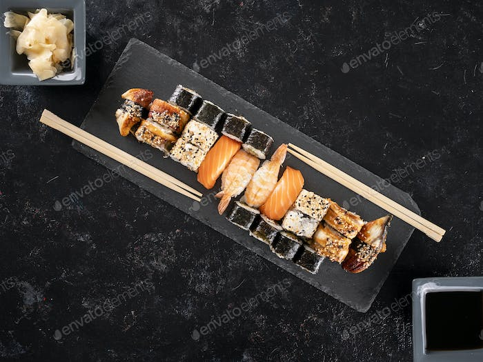 Plate of delicious healthy sushi on dark stone