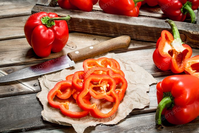 Rings of sweet pepper on paper with a knife and a whole pepper on tray.