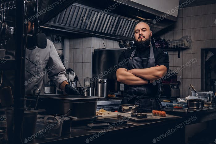 Два брутальных повара, одетые в униформу, готовят суши на кухне.