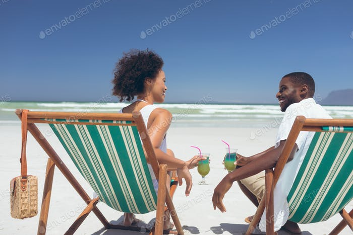 Couple relaxing on sun lounger at beach