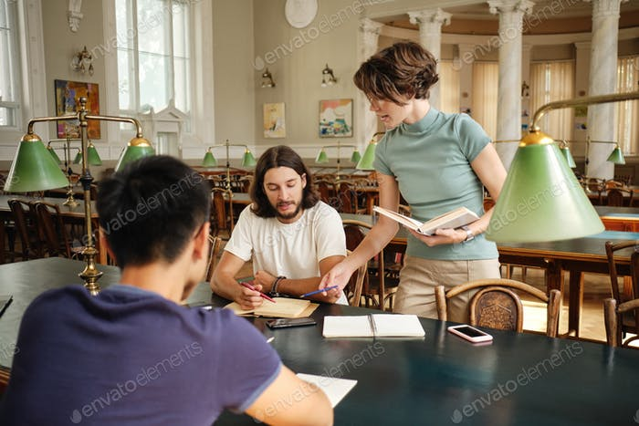 Young teacher with book explaining to students new topic during lesson in library of university
