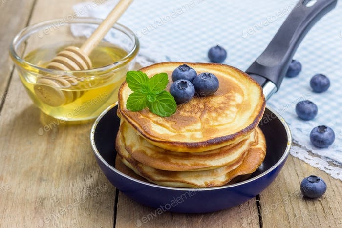 Stack of pancakes with blueberry and honey