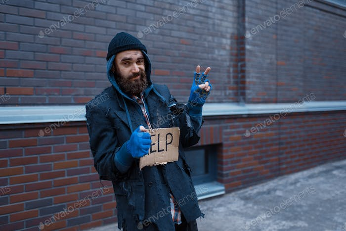 Beggar man and help sign on city street