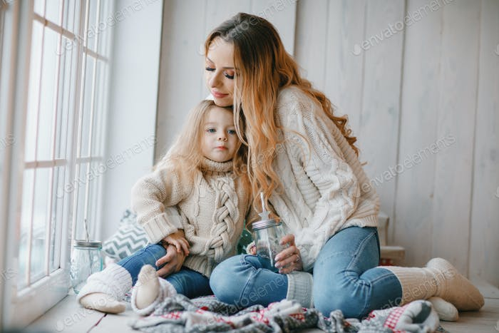 mother and daughter by the window