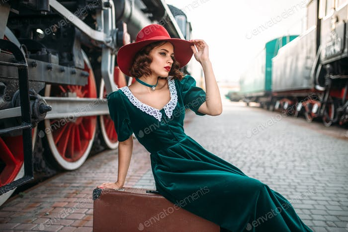 Woman sitting on suitcase against steam train