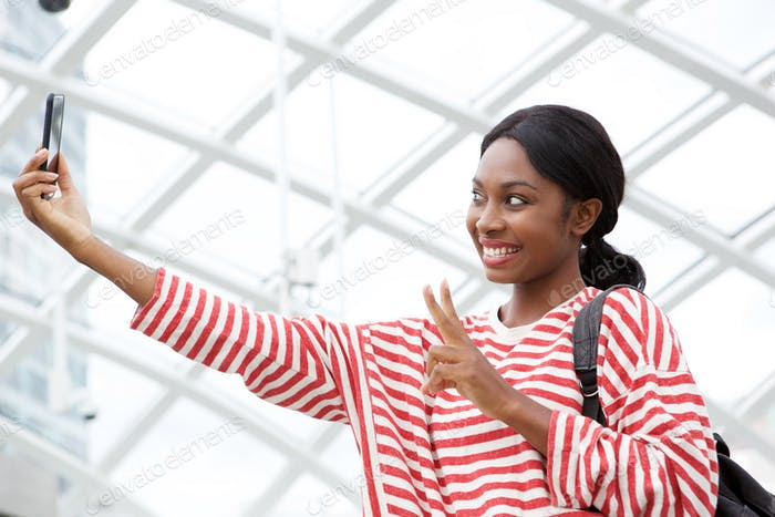 happy african american woman taking selfie with camera phone