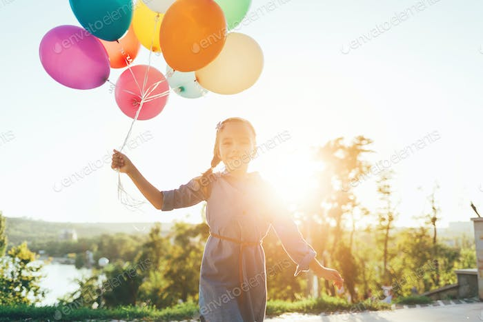 Happy girl holding colorful balloons in the city park, playing a