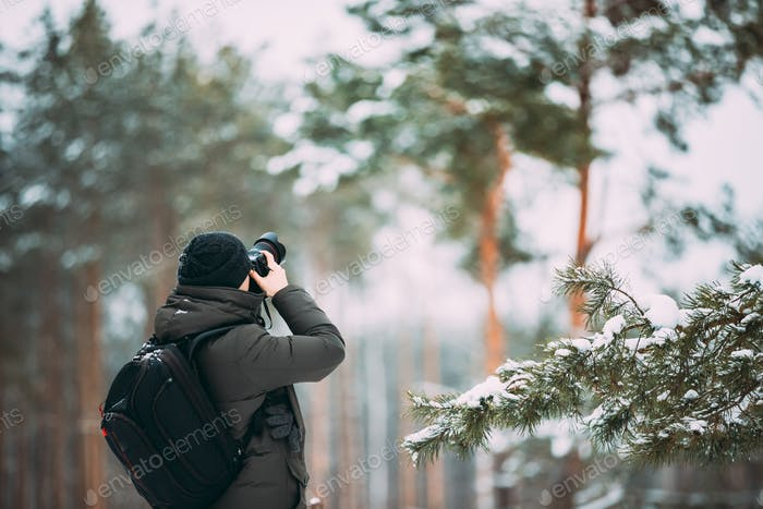 Young Man Backpacker With Photo Camera Taking Photo In Winter Sn